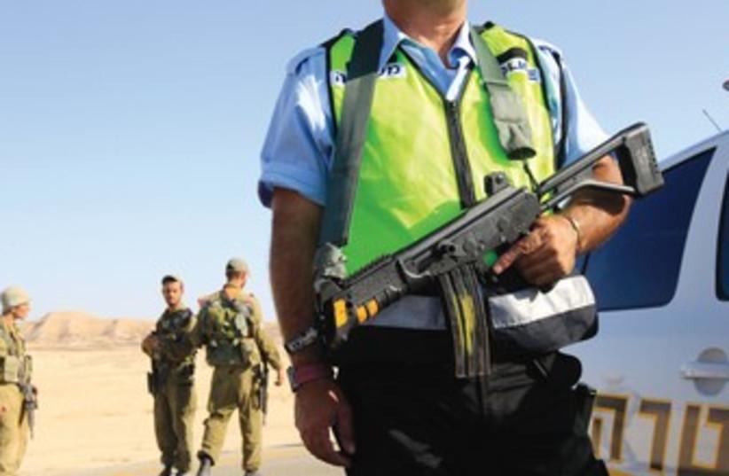 Policeman patrols near spot where a bus was ambushed 370 (photo credit: Ronen Zvulun/Reuters)