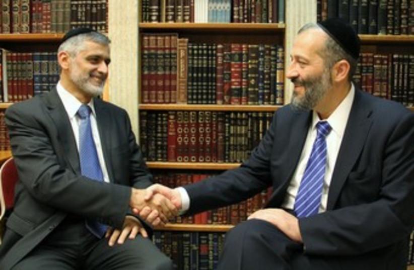 Shas's Arye Deri, Eli Yishai shake hands 370 (photo credit: Shas handout)