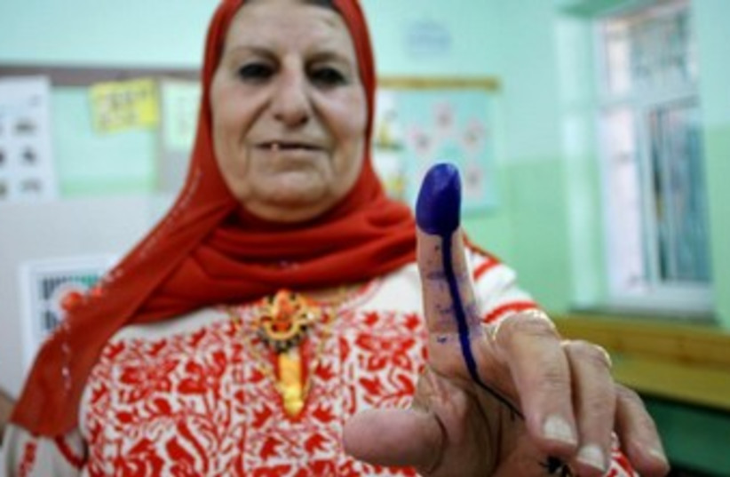 A Palestinian woman votes 370 (photo credit: Mohamad Torokman/Reuters)