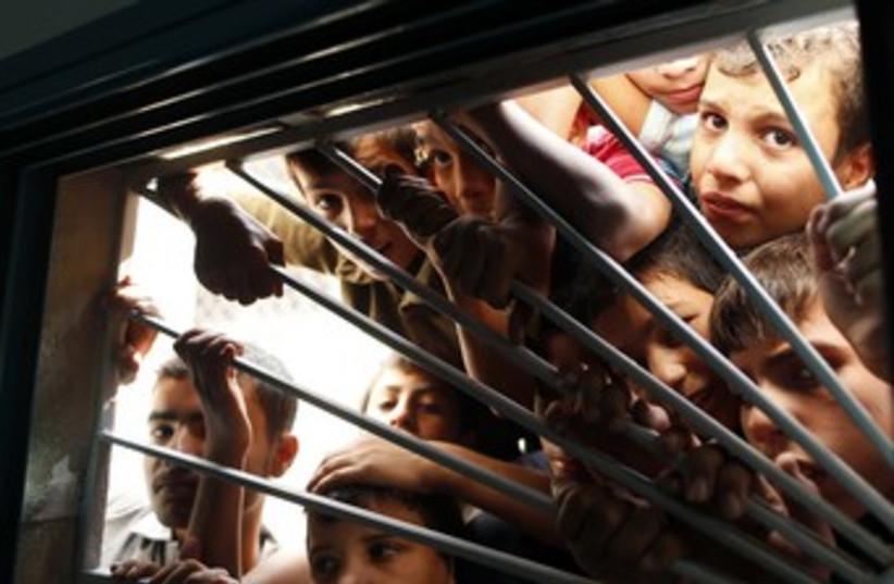 Palestinian boys look through morgue window 370 (photo credit: Reuters/Mohammed Salem)