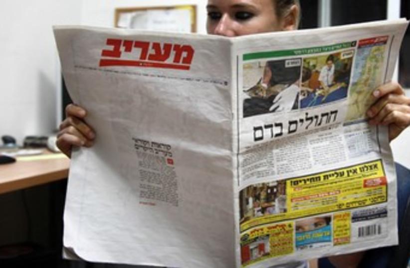 Woman reads Ma'ariv 370 (photo credit: Marc Israel Sellem/The Jerusalem Post)