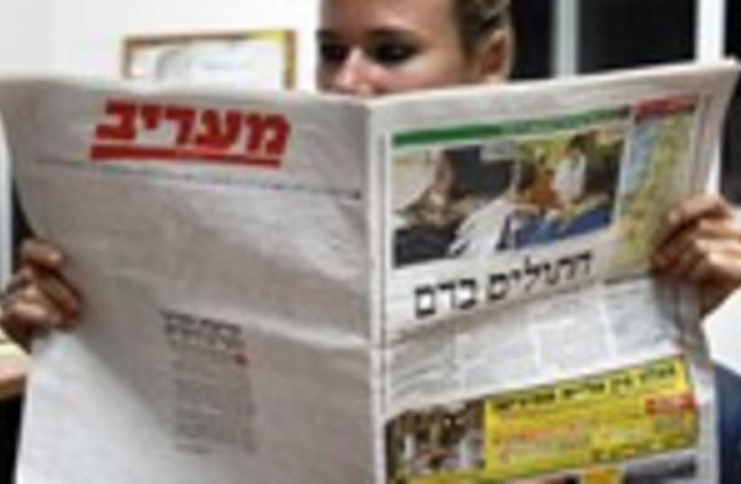 Woman reads Ma'ariv 150 (photo credit: Marc Israel Sellem/The Jerusalem Post)