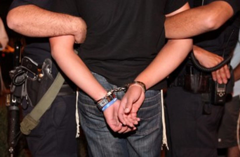 Handcuffs arrest police crime illustrative 390 (photo credit: Marc Israel Sellem/The Jerusalem Post)