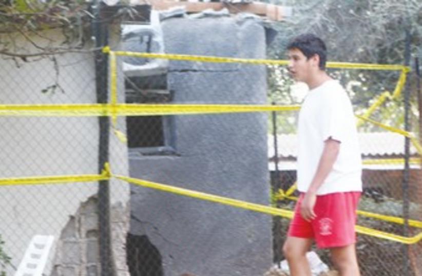 Resident surveys damaged house in Eshkol region 370 (photo credit: Ben Hartman)