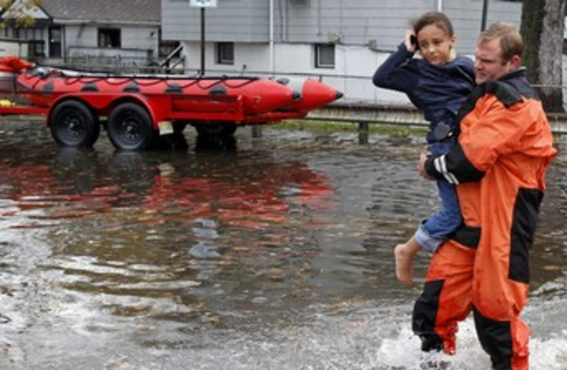Rescue worker carries girl to safety from flood waters  (photo credit: REUTERS/ Adam Hunger )