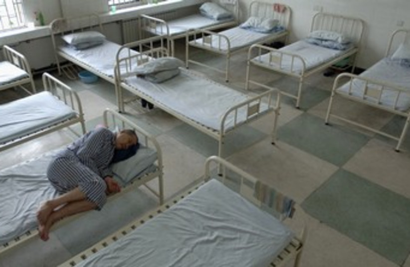 Mental health inmate rests in bed [illustrative] 370 (photo credit: REUTERS/Jianan Yu)