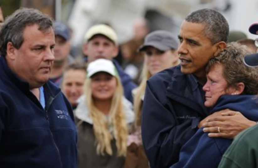 Obama and Chris Christie comfort a storm victim 370 (R) (photo credit: Larry Downing / Reuters)