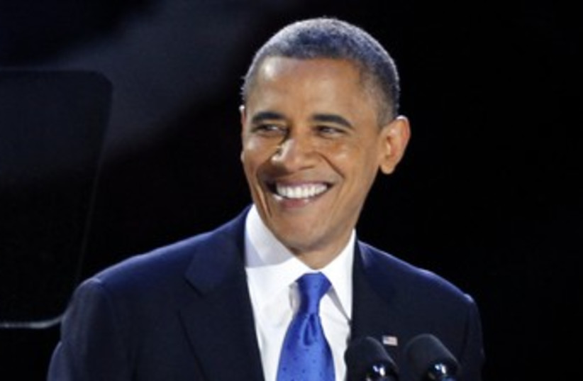 Obama smiles after winning re-election 370 (R) (photo credit: Jim Bourg / Reuters)