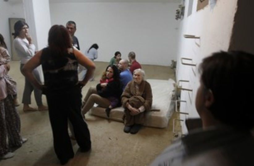 Israelis in Beersheba sit in a bomb shelter 370 (R) (photo credit: Baz Ratner / Reuters)