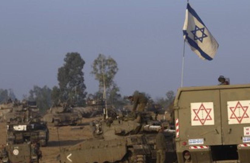 IDF tanks and a flag on the Gaza border 370 (photo credit: Ronen Zvulun / Reuters)