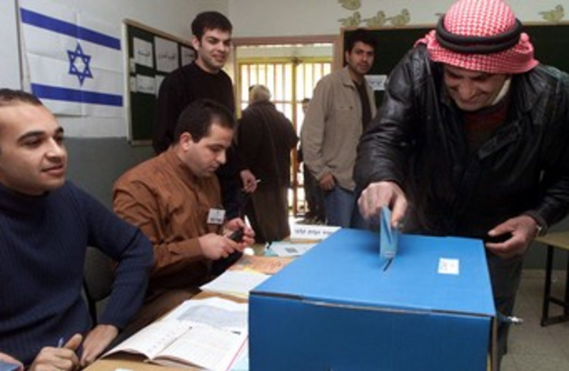 Israeli-Arab man casts his vote elections voting 370 (R) (photo credit: Ammar Awad / Reuters)
