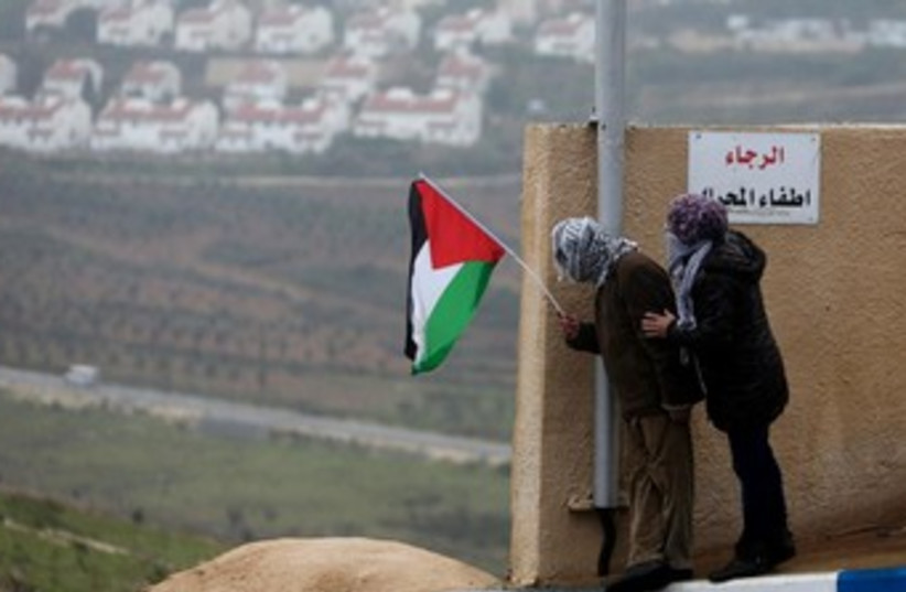 Palestinians hold a flag in the West Bank 370 (photo credit: Reuters/Mohamad Torokman)