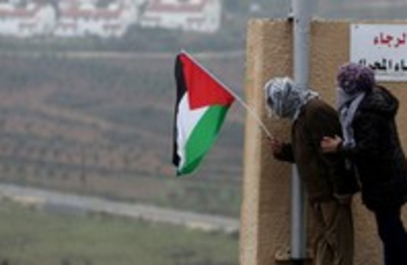 Palestinians hold a flag in the West Bank 300 (photo credit: Reuters/Mohamad Torokman)