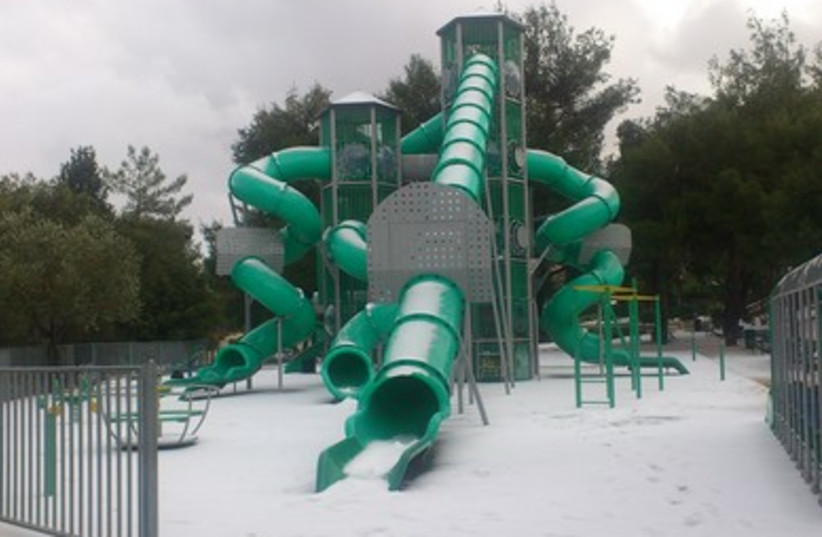 Children's playground in Gilo covered in Snow