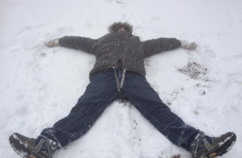 A student makes a snow-angel in Safed