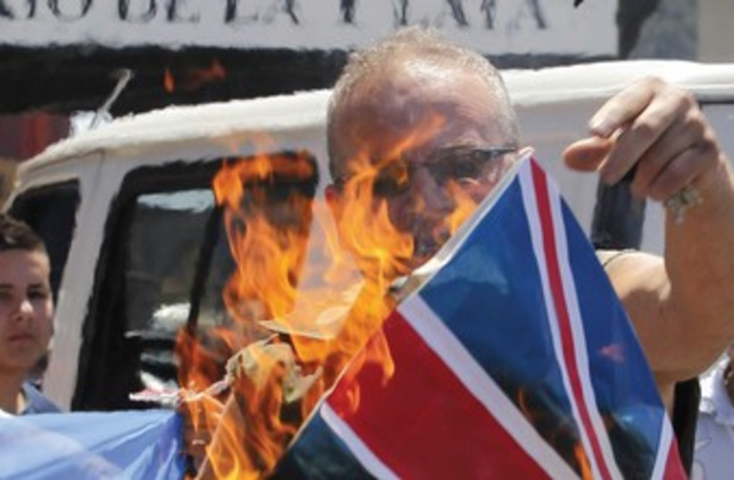 A protester burns UK flag in Argentina 370R (photo credit: Enrique Marcarian/Reuters)