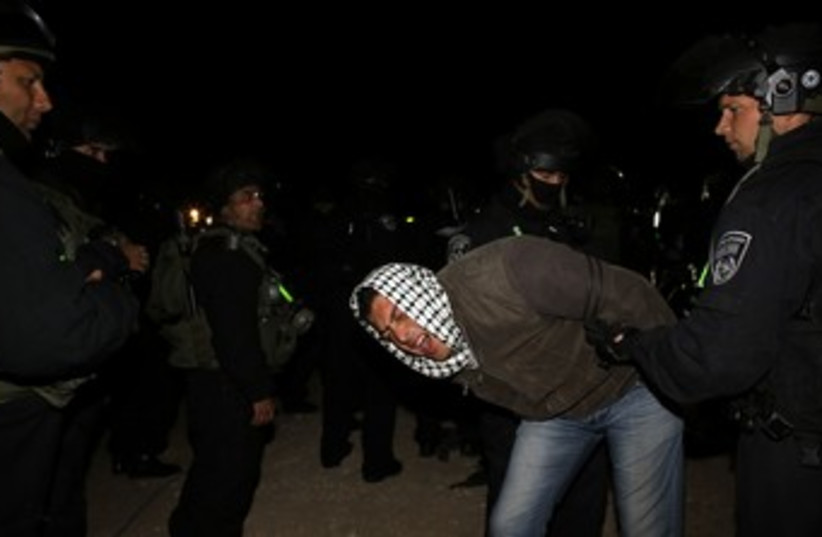 Police detain a Palestinian man at E1 outpost 370 R (photo credit: Ammar Awad / Reuters)