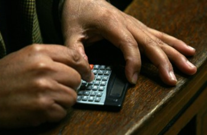 An accountant calculator taxes 370 (photo credit: Ivan Alvarado / Reuters)