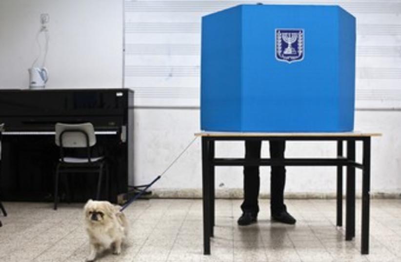 A Tel Aviv man votes with his dog 370 (photo credit: Nir Elias/Reuters)