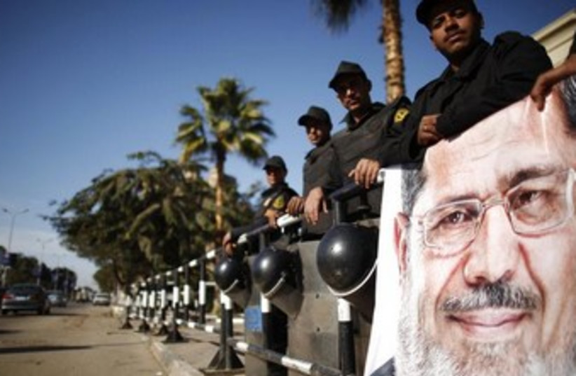 Policemen stand guard near Morsi poster 370 (photo credit: REUTERS/Khaled Abdullah)
