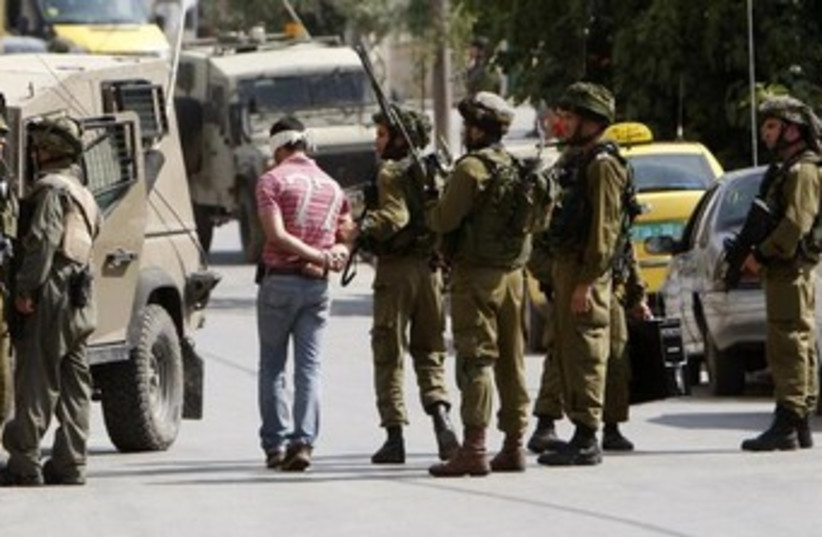 IDF soldiers arrest Palestinian 370 (photo credit: REUTERS/Mohamad Torokman)