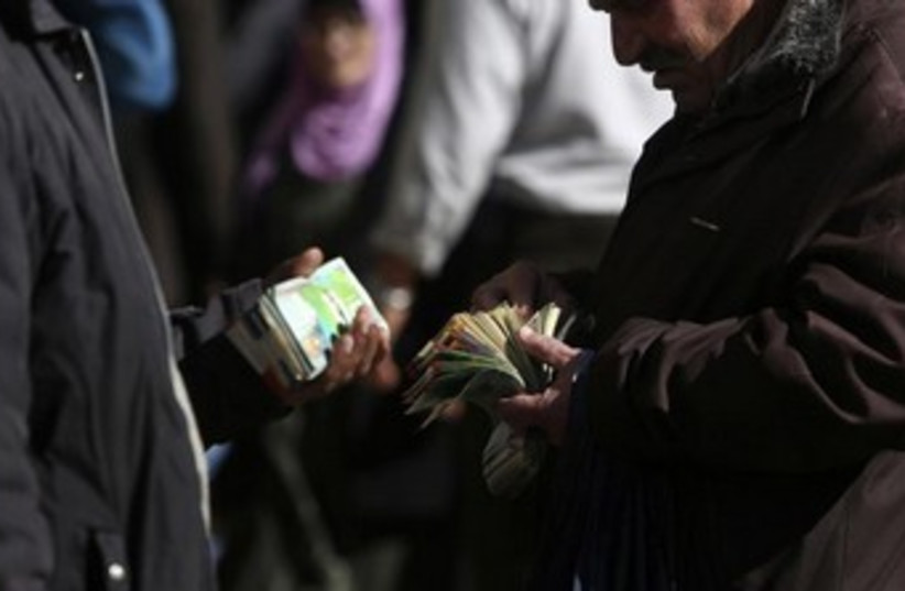 Palestinian money changers 370 (photo credit: REUTERS/Mohamad Torokman)