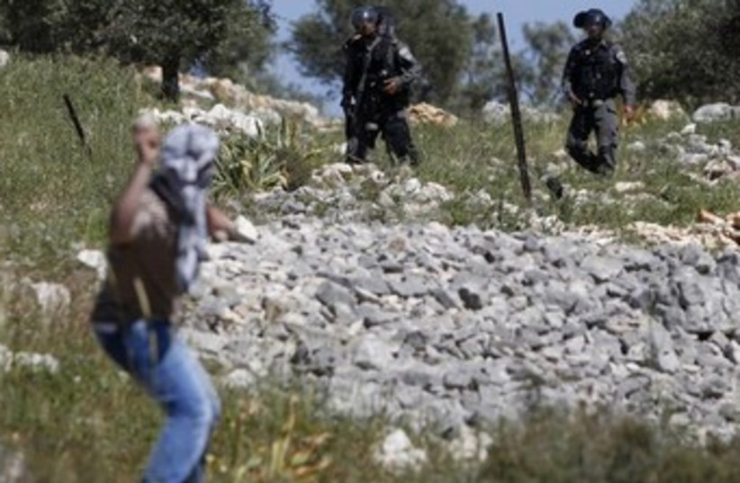 Palestinian throwing stones at Israeli border police 370 (photo credit: REUTERS/Mohamad Torokman)