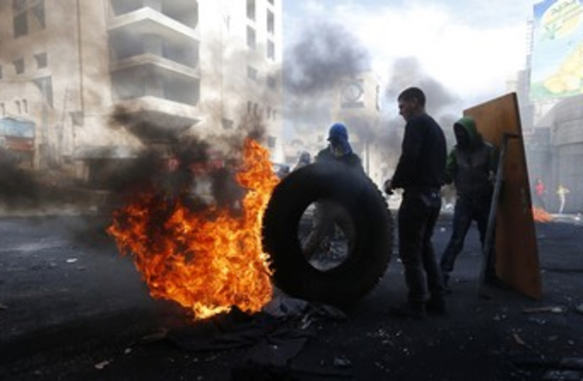Palestinian protesters next to burning tyre in Hebron 370 (photo credit: reuters)