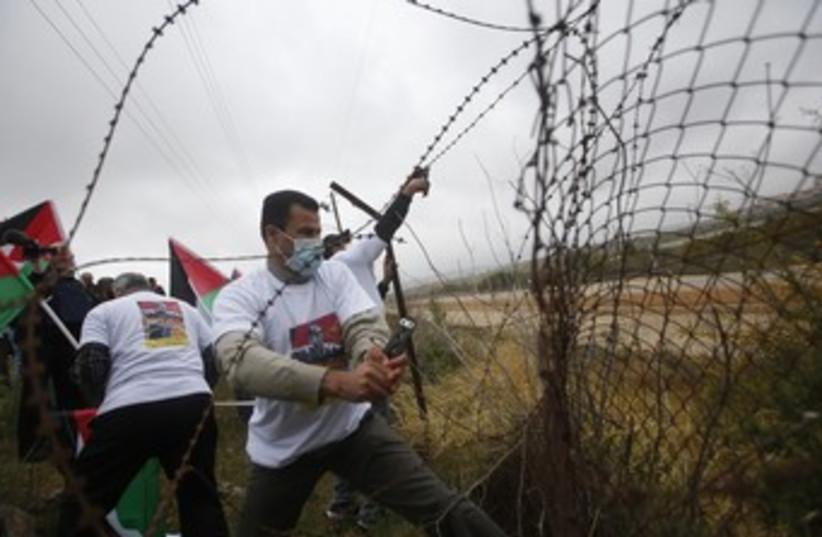 Palestinian activists cut a part of a fence (photo credit: REUTERS/Mohamad Torokman)