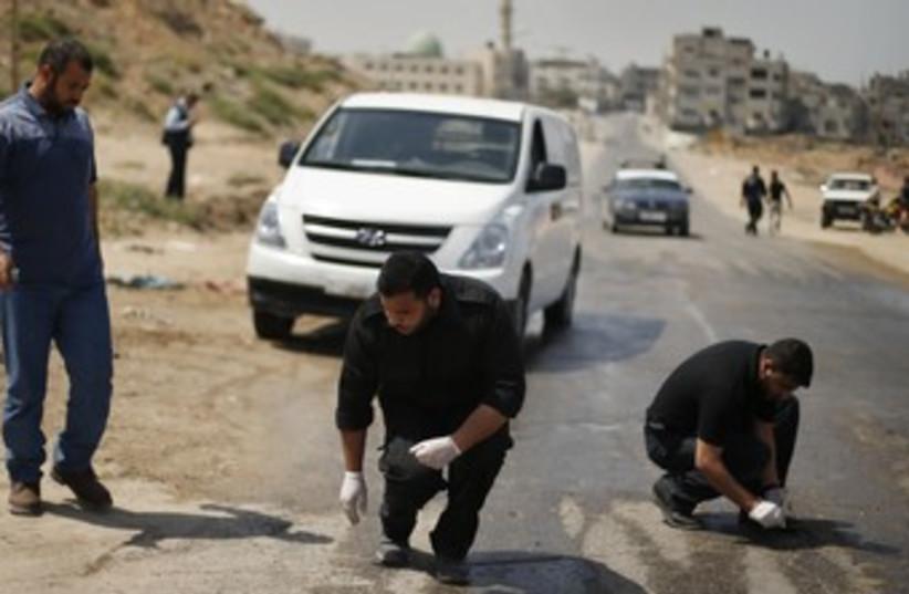 Palestinian police inspect scene after IAF strike, Gaza 370 (photo credit: REUTERS)