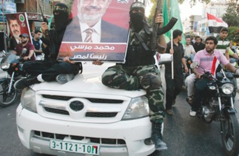 Hamas gunmen hold Morsi poster 370 (photo credit: Mohammed Salem/Reuters)