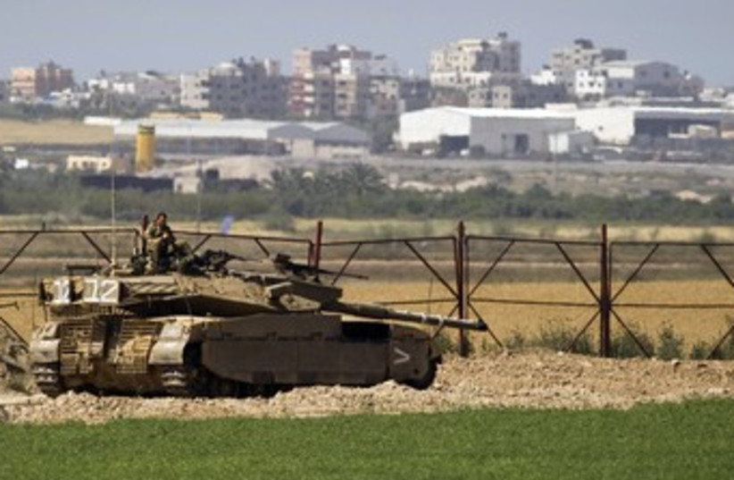 IDF soldier sits atop a tank just outside northern Gaza 370 (photo credit: REUTERS/Amir Cohen)