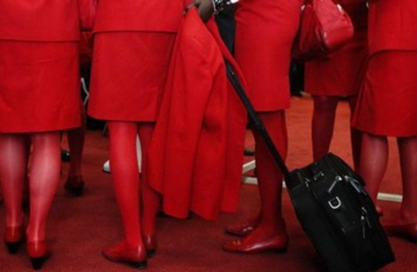 Airline stewardesses wearing red (photo credit: REUTERS/Heinz-Peter Bader)