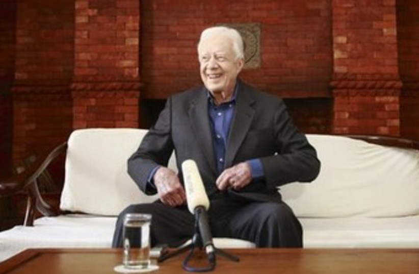 Jimmy carter smiling from couch 370 (photo credit: REUTERS)