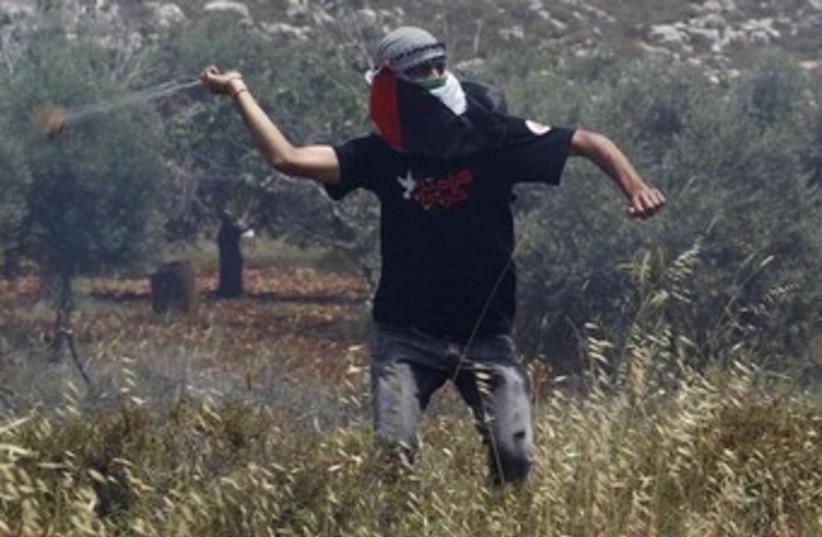 Palestinian uses slig to throw rocks 370 (photo credit: REUTERS/Mohamad Torokman)
