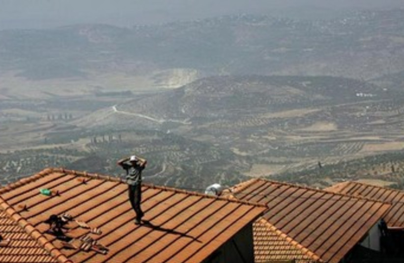 jewish settlers stands on a house Homesh in 2005 370 (photo credit: REUTERS)