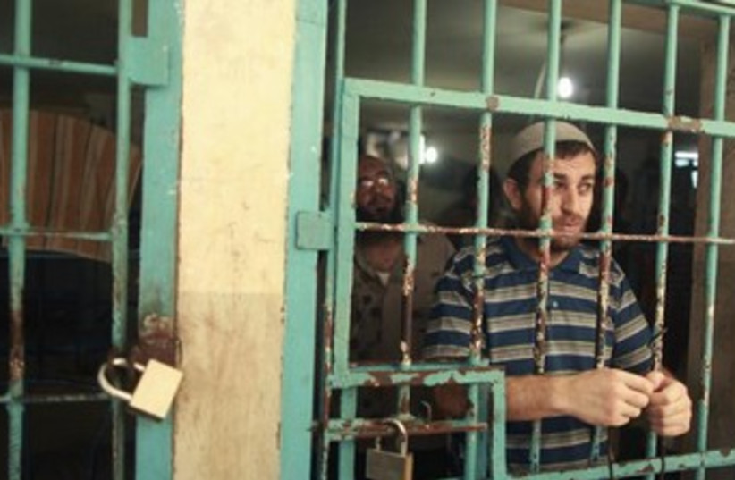 Gazan behind prison bars 370 (photo credit: REUTERS/Mohammed Salem )