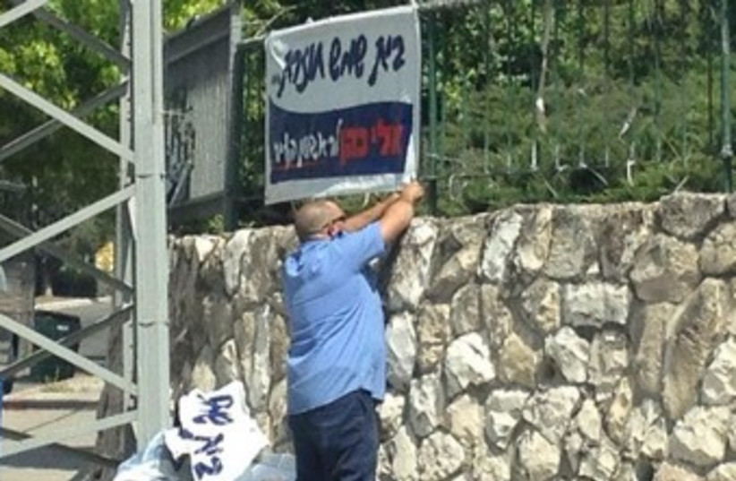 Bet Shemesh worker removing campaign poster 370 (photo credit: Courtesy Eli Cohen campaign Facebook page.)