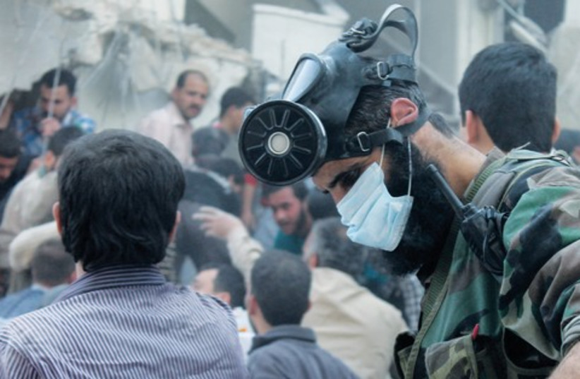 A man wearing a chemical mask searches for survivors (photo credit: Haleem Al-Halabi/Reuters)