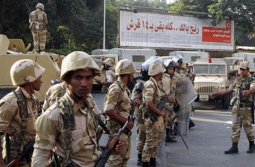 Egyptian army stands guard near Morsi supporters370 (photo credit: REUTERS)