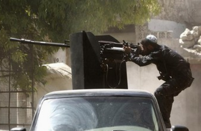 Syrian Islamist rebel shoots big gun 370 (photo credit: REUTERS)