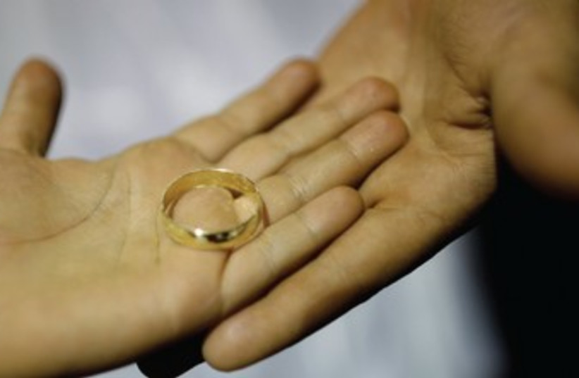 Couple holding a wedding rings 370 (photo credit: REUTERS)