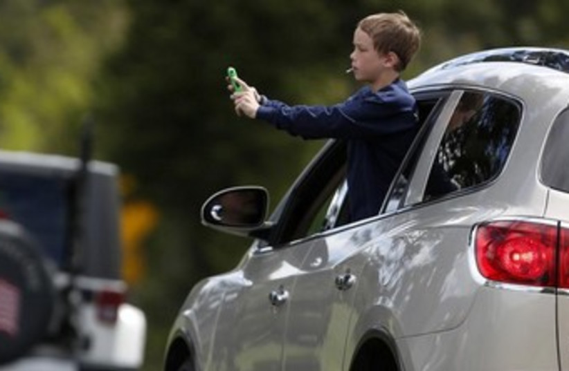 A child leans out the window of a moving car 370 (photo credit: REUTERS)