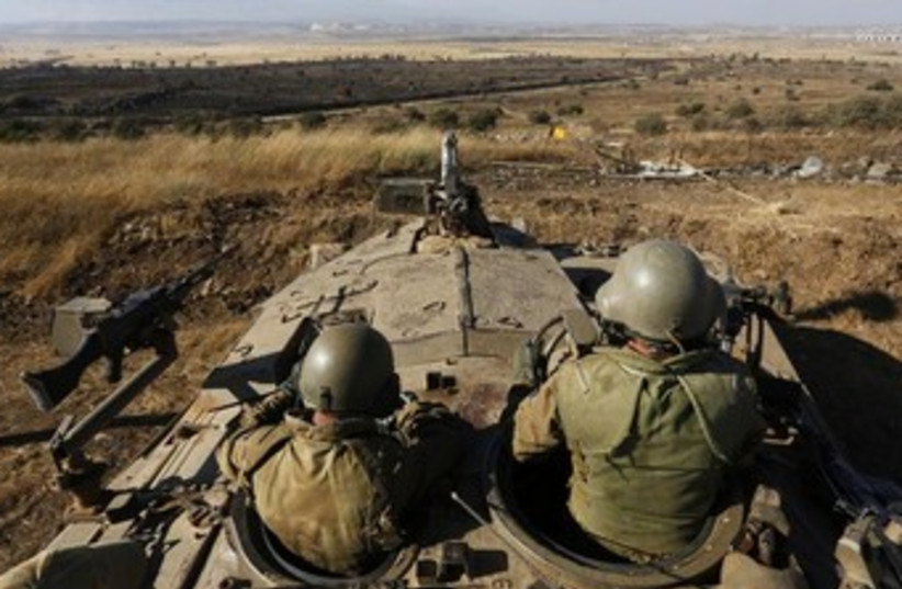 IDF troops survey golan heights 370 (photo credit: REUTERS)
