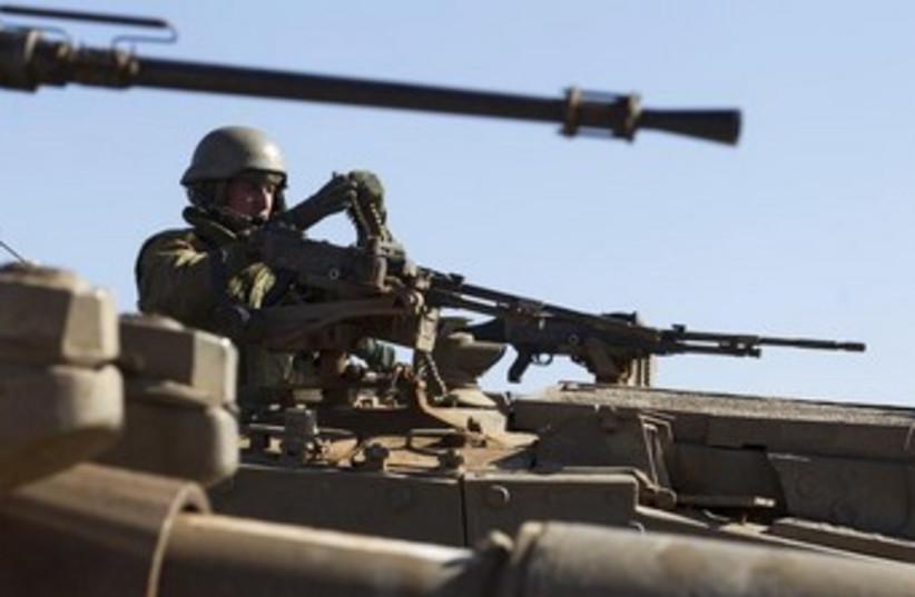 An Israeli soldier arranges ammunition atop a tank 370 (photo credit: REUTER/Baz Ratner)