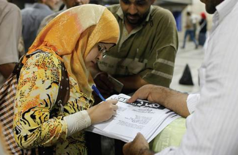 A woman signs petition in support of the anti-Morsi movement (photo credit: ASMAA WAGUIH / REUTERS)