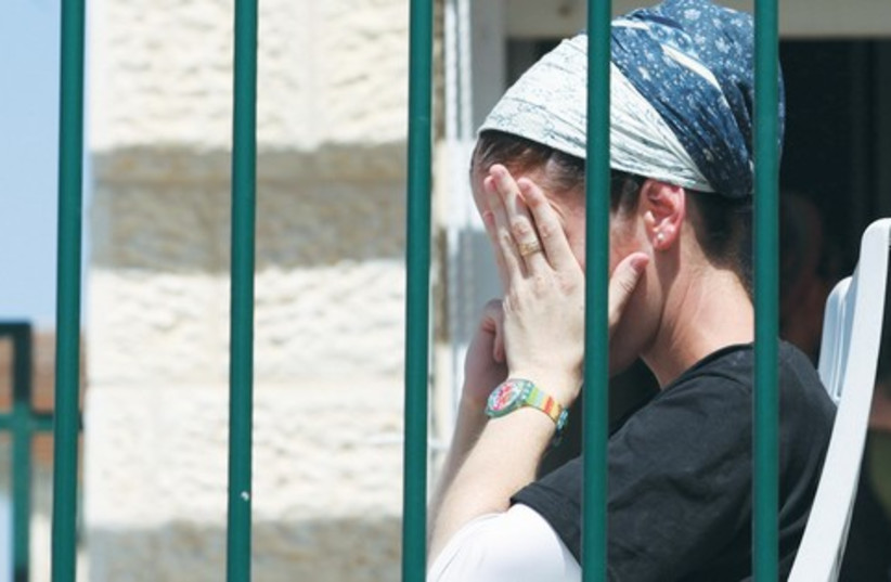 Religious woman covering face behind bars (photo credit: Marc Israel Sellem)