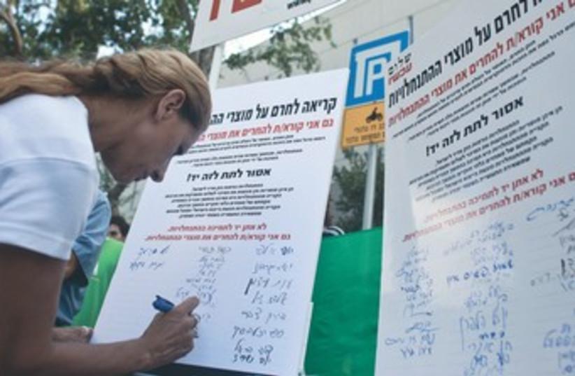 Woman signs Peace Now petition against settlements 370 (photo credit: Reuters)