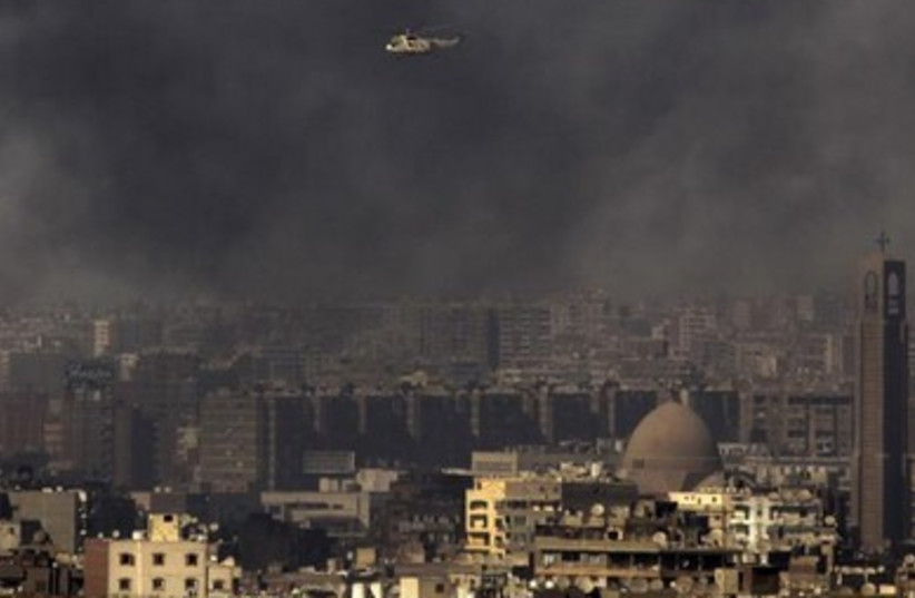 A military helicopter flies over clouds of smoke in Cairo July 26, 2013.