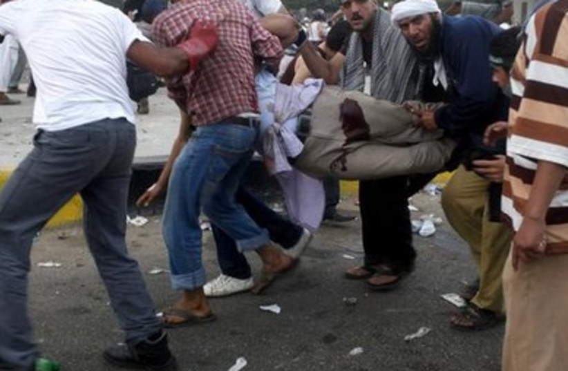 Morsi supporters carry injured man in Nasr City, July 27, 2013.